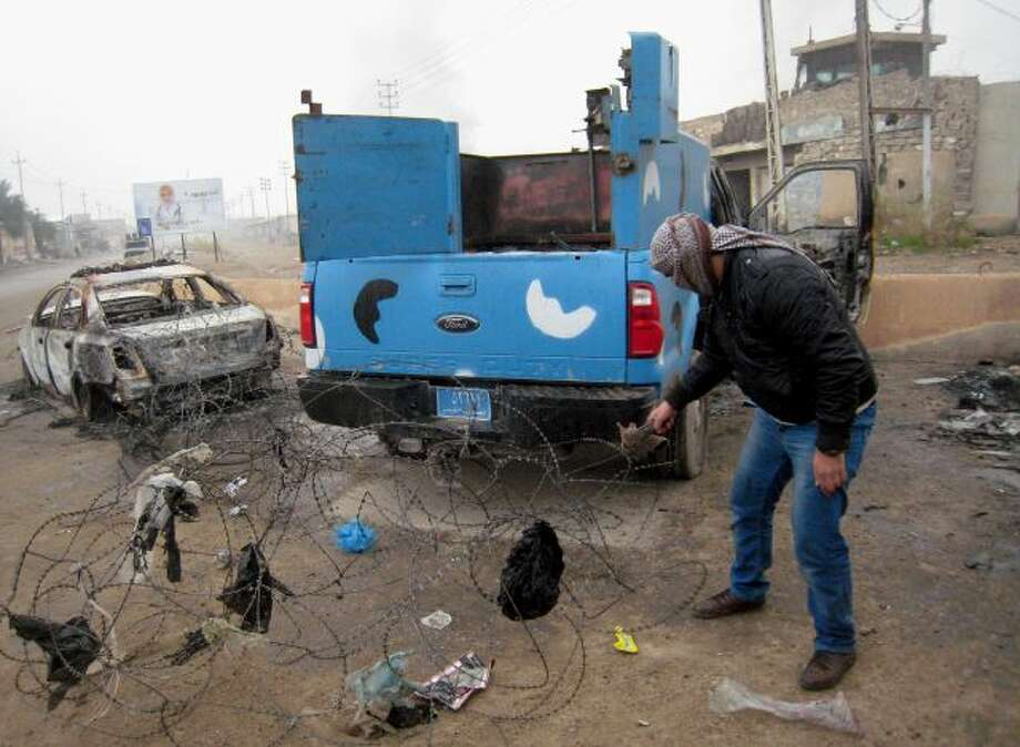 FILE - In this Friday, Jan. 10, 2014 file photo, a masked anti-government gunman clears debris after clashes in Fallujah, Iraq. Islamic militants who took over the Iraqi city of Fallujah are now trying to show they can run it, providing social services, policing the streets and implementing Shariah rulings in a bid to win the support of its Sunni Muslim population. (AP Photo, File) Photo: AP / AP