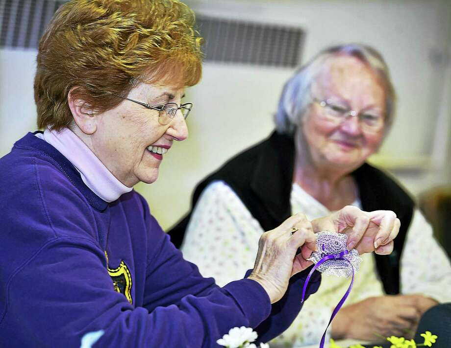 (Catherine Avalone - New Haven Register)   Parishoners Shelby Zold, at left, and Mary Harris worked together to create one of the many bonnet pins at the Easter Hat Challenge Workshop at Orange Congregational Church. The bonnet pins will be provided to women attending the Easter service who chose not to wear an Easter hat or bonnet. Photo: Journal Register Co. / New Haven RegisterThe Middletown Press