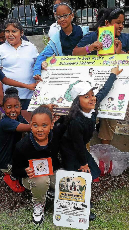 On Monday officials with Audubon Connecticut and the U.S. Fish and Wildlife Service visited the school to honor students and teachers for transforming the grounds that encircle the buildingís play area into what they hope will become a bird sanctuary. Students shown here are proud of their new sign, created using artwork they did themselves. (Evan Lips - New Haven Register) Photo: Journal Register Co.