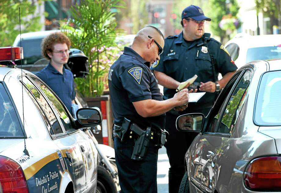 (Peter Hvizdak - New Haven Register) New Haven Police officers Hector Valentin, center, and Robert DuPont, right, on Orange Street near Chapel Street in New Haven write warnings for vehicles that did not properly yield to pedestrians at the crosswalk on Orange and Court Streets Tuesday, July 28, 2015. In cooperation with the NHPD, New Haven's Department of Transportation, Traffic and Parking intern Jacob Wasserman, a Yale University Dwight Hall Rising Star Fellow, left,  gave away gift-cards to Tikkaway Grill in New Haven for those motorists who  properly yielded to pedestrians in crosswalks. All motorists received information from the City's Street Smarts and Go New Haven Go campaigns. Photo: ©2015 Peter Hvizdak / ?2015 Peter Hvizdak