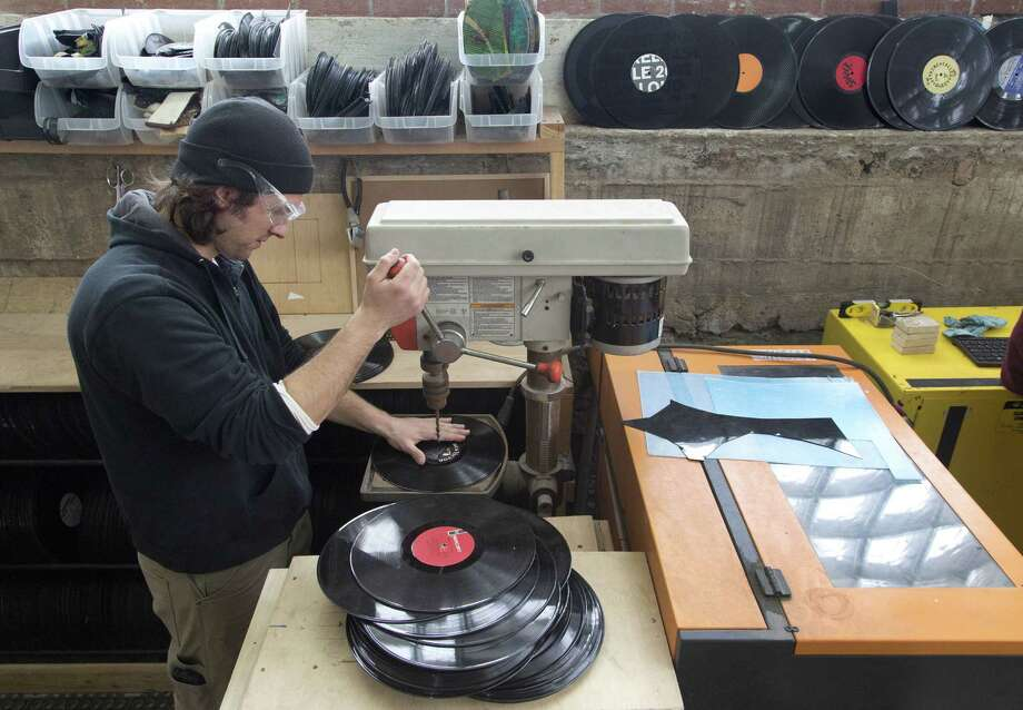 George Kamen uses a drill press to prepare records before they are made into decorative clocks at Wrecords By Monkey. Photo: Mark Lennihan — The Associated Press  / AP
