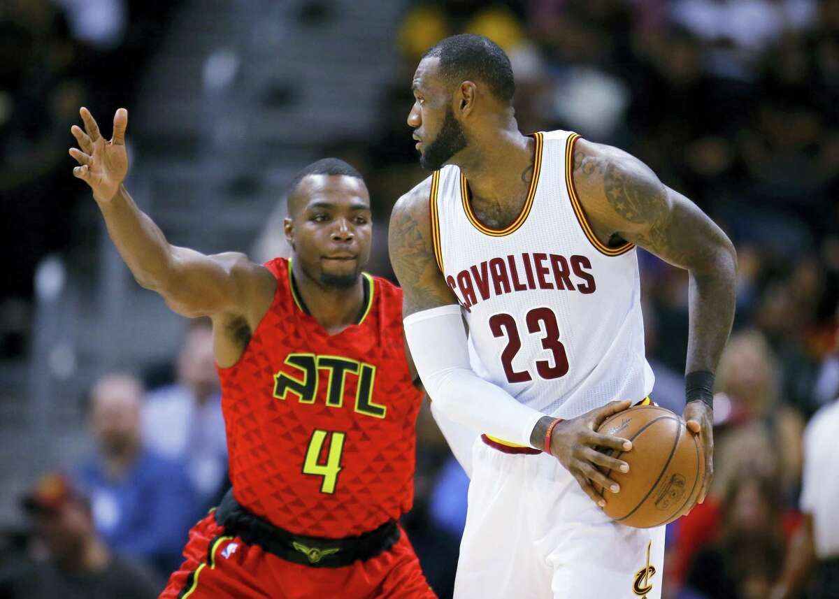 Cleveland Cavaliers forward LeBron James (23) is defended by Atlanta Hawks forward Paul Millsap (4) in the first half of an NBA basketball game on Sunday, April 9, 2017, in Atlanta. The Hawks won in overtime 126-125. (AP Photo/Todd Kirkland)