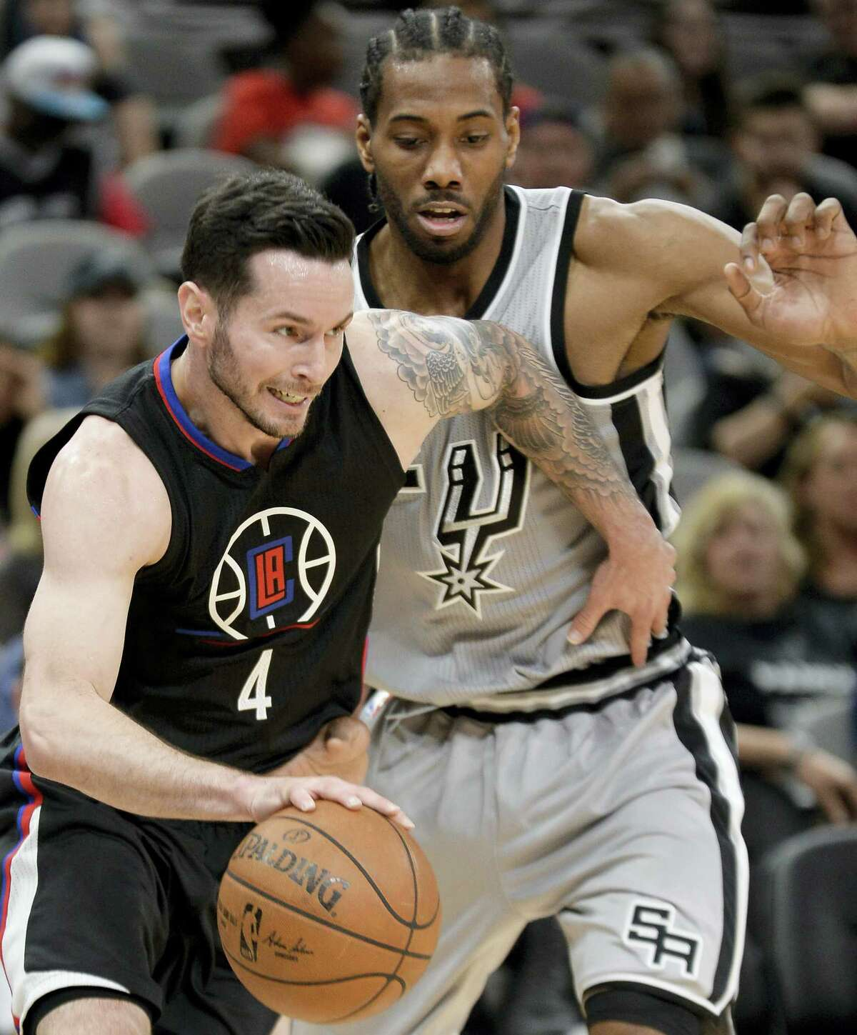 Los Angeles Clippers guard J.J. Redick (4) drives around San Antonio Spurs forward Kawhi Leonard during the first half of an NBA basketball game, Saturday, April 8, 2017, in San Antonio. (AP Photo/Darren Abate)