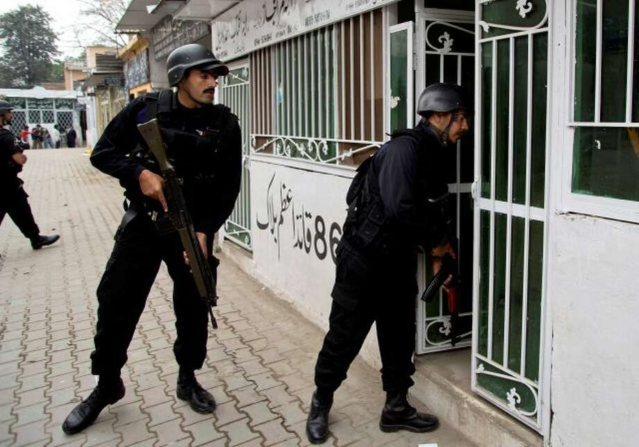 Pakistani police commandos search inside lawyers offices looking for attackers following a suicide attack in a court complex, in Islamabad, Pakistan, Monday, March 3, 2014. Two suicide bombers blew themselves up at a court complex in the Pakistani capital on Monday, killing nearly a dozen and wounding scores in a rare terror attack in the heart of Islamabad, officials said. (AP Photo/B.K. Bangash) Photo: AP / AP