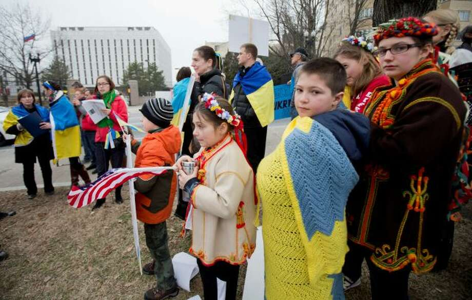 Siblings Oriana Piazza, holding American flag, center, Maksim Piazza, foreground second from right, and Sofijka Piazza, right, who are of Ukrainian descent, join a protest rally in front of the Russian embassy, back left white building, in Washington, Sunday, March 2, 2014. Igniting a tense standoff, Russian forces surrounded a Ukrainian army base Sunday just as the country began mobilizing in response to the surprise Russian takeover of Crimea. Outrage over Russia's tactics mounted in... Photo: AP / AP