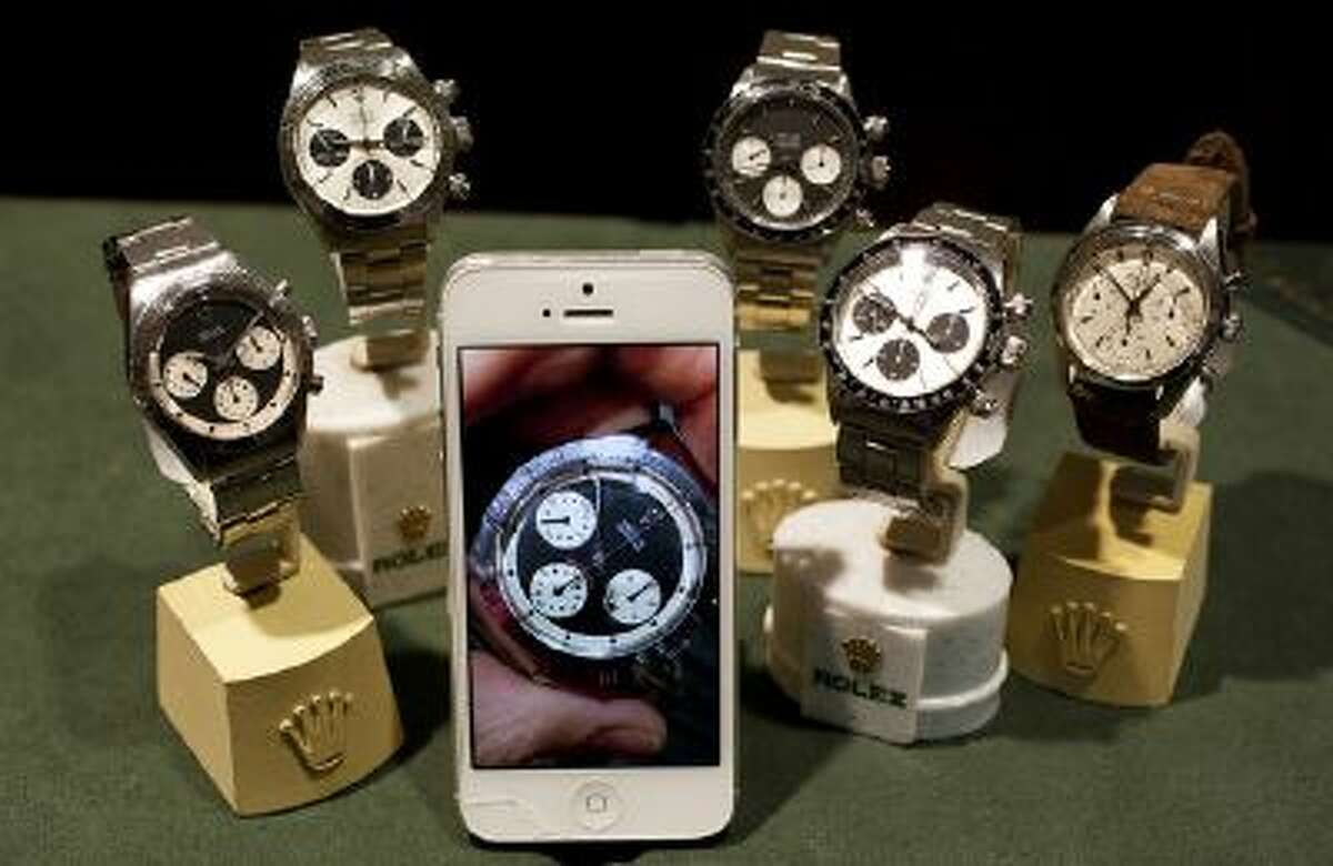 A photo of a Paul Newman Rolex Daytona on Kris Bonifas' iPhone sits with an actual Rolex Daytona's at left, and other Rolex watches at FourtanÈ in Carmel-by-the-Sea, Calif., on Thursday, July, 11, 2013.