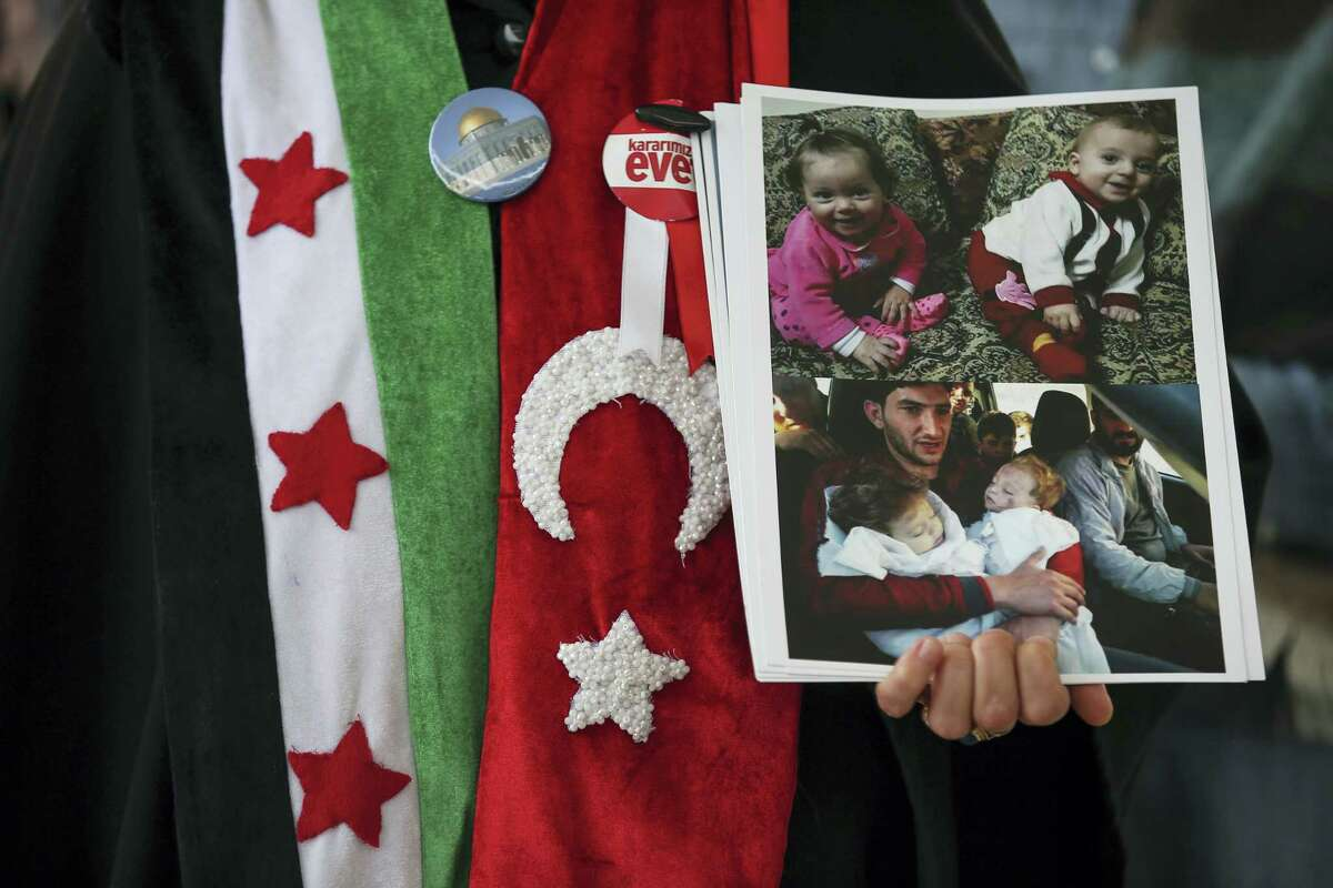 A protester holds pictures of people she asserted were victims of the recent suspected chemical attack in Idlib, Syria, in Istanbul, Friday, April 7, 2017. Some hundreds of people gathered in the courtyard of the mosque in Istanbul following Friday prayers to protested against the attack and prayed for the victims. (AP Photo/ Emrah Gurel)