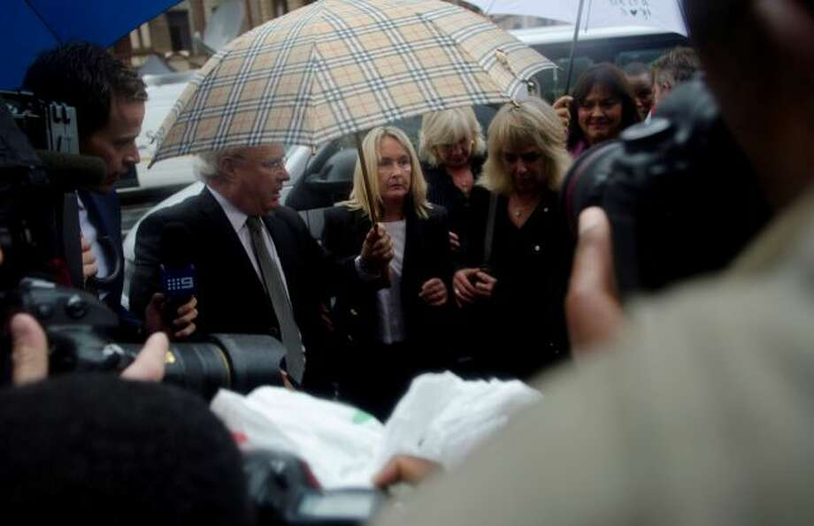 June Steenkamp, center under umbrella, the mother of Reeva Steenkamp, arrives at the High Court in Pretoria, South Africa, Monday, March 3, 2014. Athlete Oscar Pistorius is charged with murder with premeditation in the shooting death of his girlfriend Reeva Steenkamp in the pre-dawn hours of Valentine's Day 2013. (AP Photo/Skyler Reid) Photo: AP / AP