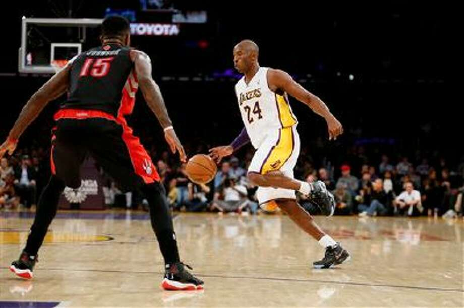 Los Angeles Lakers' Kobe Bryant dribbles the ball as Toronto Raptors' Amir Johnson, left, defends during the first half of an NBA basketball game in Los Angeles, Sunday, Dec. 8, 2013. (AP Photo/Danny Moloshok) Photo: AP / FR161655 AP