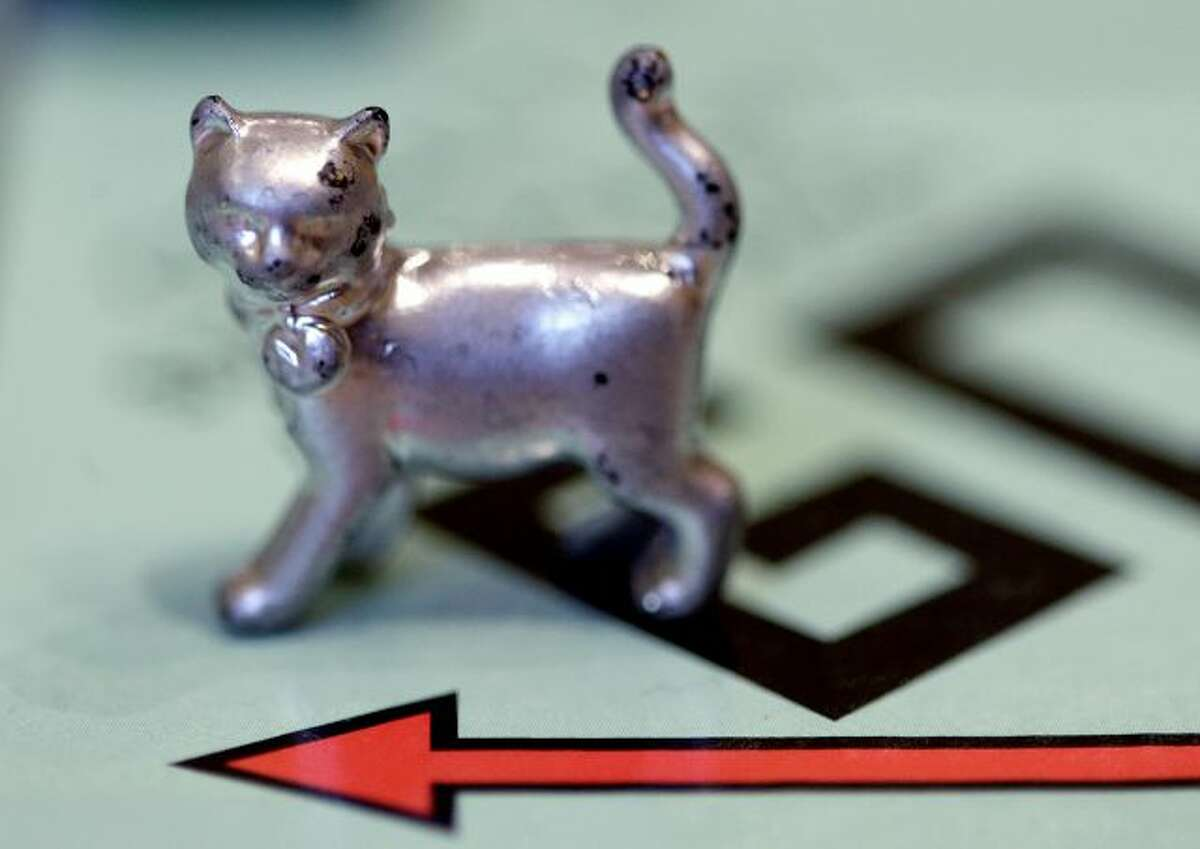 """FILE - This Feb. 5, 2013 file photo shows a cat token, the newest Monopoly token on the game board at Hasbro Inc. headquarters, in Pawtucket, R.I. Hasbro has released a limited """"house rules"""" edition of the popular board game. (AP Photo/Steven Senne, File)"""