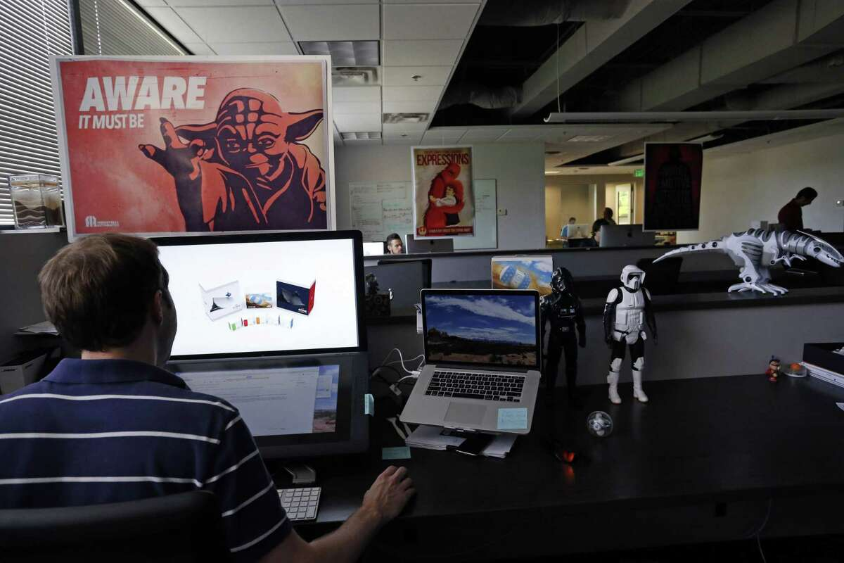 In this July 24, 2015 photo, an employee at Sphero, a fast-growing toy robotics company, works surrounded by Star Wars toys and posters, at the company headquarters in Boulder, Colo. The company has collaborated with Lucasfilm-parent Disney to develop the BB-8, a droid character which will be featured in ìStar Wars: Episode VII - The Force Awakens.î (AP Photo/Brennan Linsley)