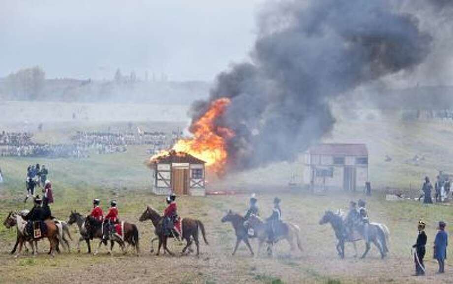 Troops march in front of a burning house during the reconstruction of the Battle of the Nations at the 200th anniversary near Leipzig, central Germany, Sunday, Oct. 20, 2013.