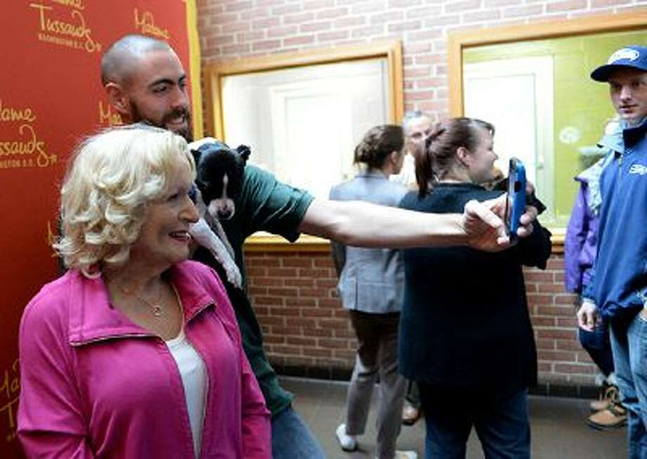 """Washington Animal Rescue League's George Scharffenberger takes a selfie with Betty White's wax Madame Tussaud's figure along with a puppy """"Elroy"""" at the Rescue League on October 10 in Washington. The wax figure is on loan to the Washington outpost of Madame Tussaud's from the Hollywood branch of the museum. The wax figures are sometimes provided for charitable events."""