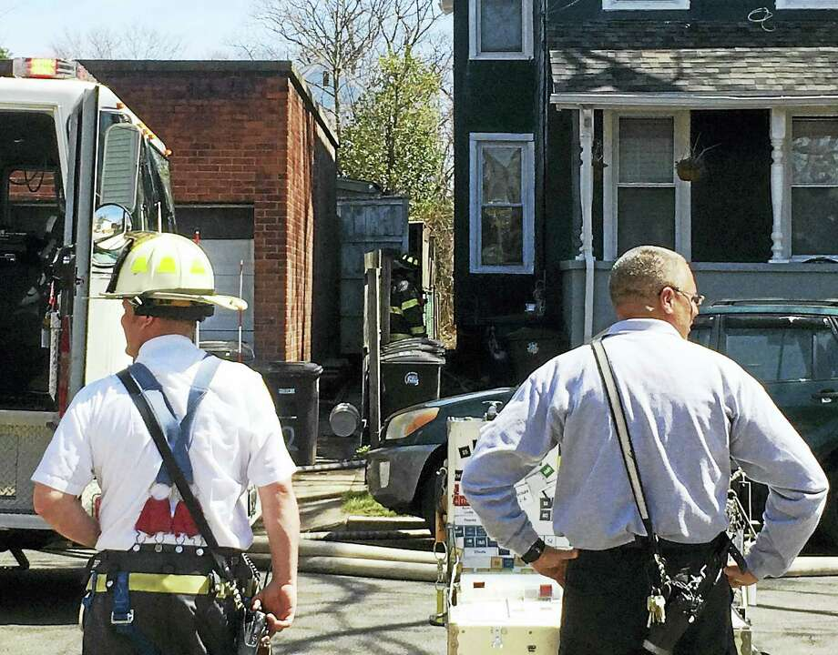 (Wes Duplantier/New Haven Register) City firefighters responded to a brush fire between a house and a garage late Monday morning on Greenwich Avenue in New Haven. No one was hurt in the fire, which did minor damage to the home. Photo: Journal Register Co.