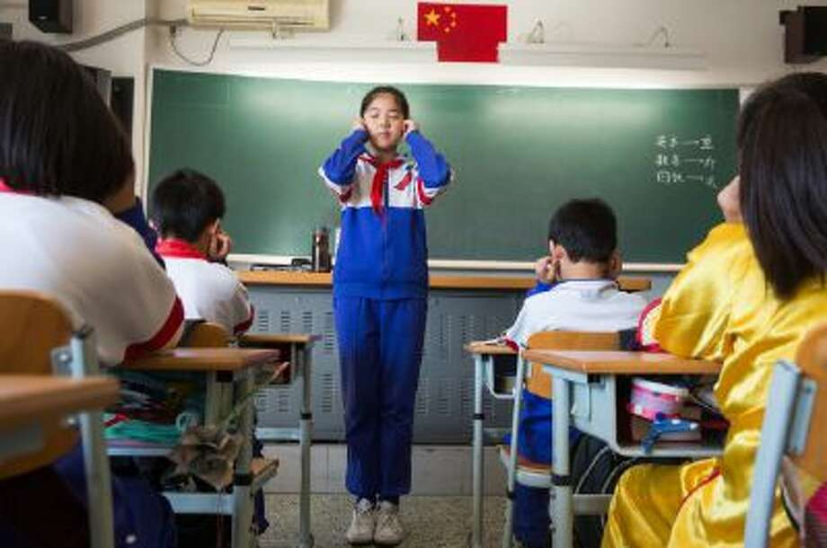 In a Primary 5 class at Jingshan School, one of Beijing's most elite schools, pupils take a few minutes to do eye exercises to help relax their eyes.