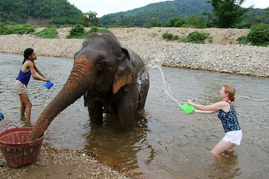 The author, Lillian Cunningham, right, and another visitor help bath an elephant at the Elephant Nature Park; the elephants roam free across 250 acres of parkland, one of the few rescue outposts in Thailand. (Anucha Jiwju) / Anucha Jiwju