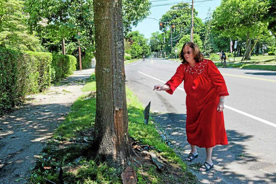 (Melanie Stengel - Register)   A homeowner who did not wish to be named, picks up debris from the fatal car crash, in front of her house, this morning 7/6. She says that this is the third accident at this spot in recent history. She also said that part of the car landed on her front porch. The car hit a tree, skid, became airborn, hitting two more trees. Photo: Journal Register Co.