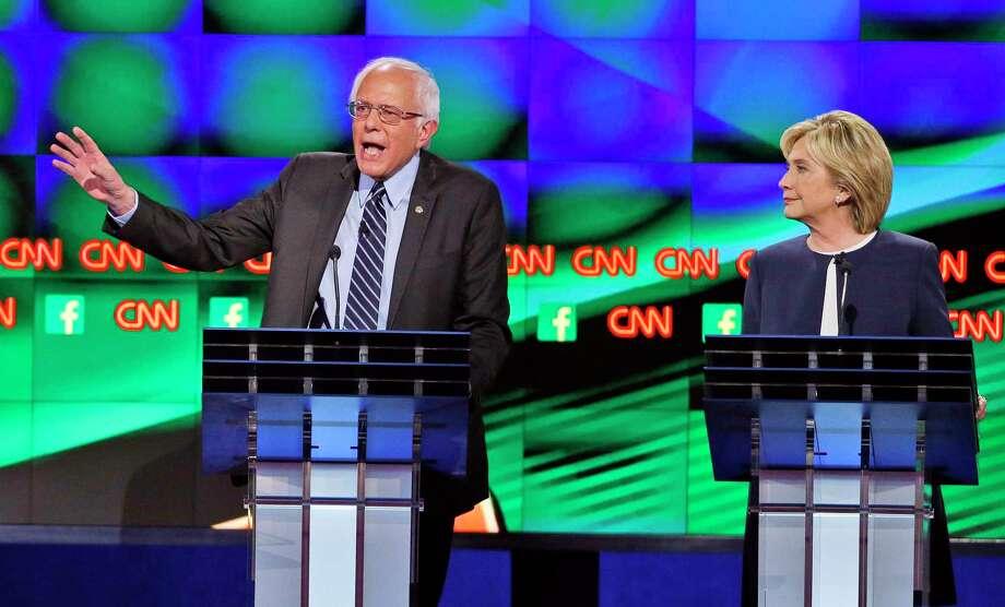 Sen. Bernie Sanders, left, speaks as Hillary Rodham Clinton looks on during Tuesday's debate. (John Locher — The Associated Press) Photo: AP / AP