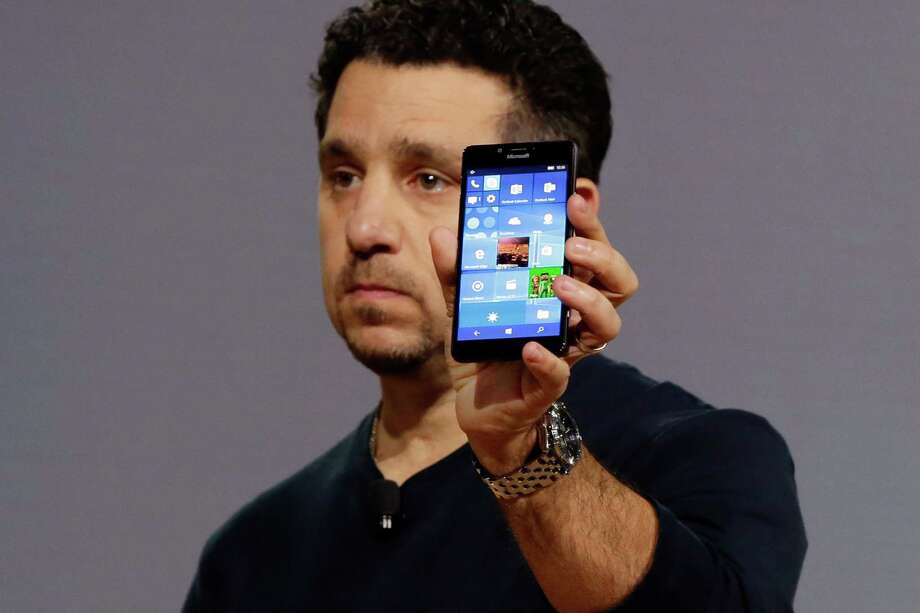 Microsoft vice president for Surface Computing Panos Panay shows a new Lumia 950 phone. The device will work with an optional dock. Users can attach a regular monitor, keyboard and mouse and work with apps on the phone just like you would on a Windows 10 desktop. (AP Photo/Richard Drew) Photo: Richard Drew — The Associated Press  / AP