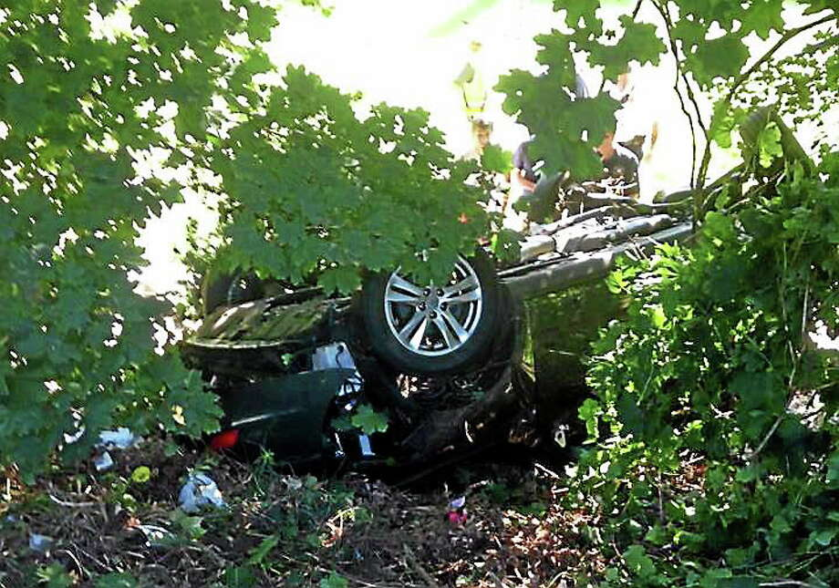 The driver of an SUV escaped with only minor injuries Monday after he lost control of his vehicle on Route 8 in Derby, flipping over and landing on its roof in the backyard of a home on Mohawk Avenue. (Contributed photo/Tracy's Service Station & Garage) Photo: Journal Register Co.