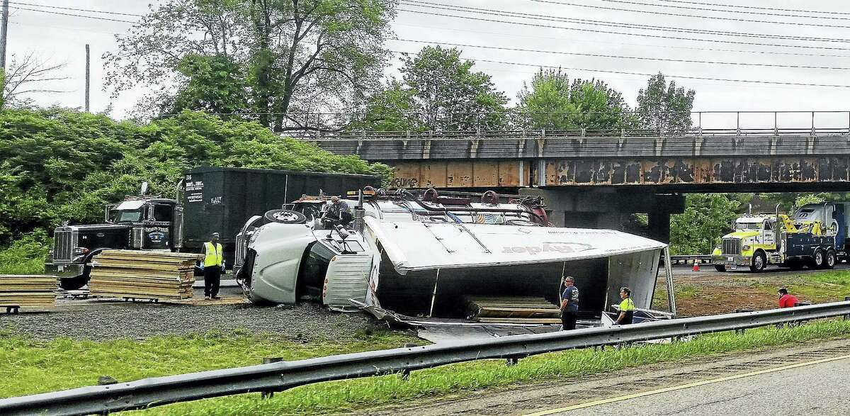 (Photos by Kathleen Schassler/Digital First Media) A tractor-trailer overturned and crashed Tuesday morning on Interstate 91 northbound in Wallingford. The crash caused severe delays on the northbound and southbound sides of the highway.