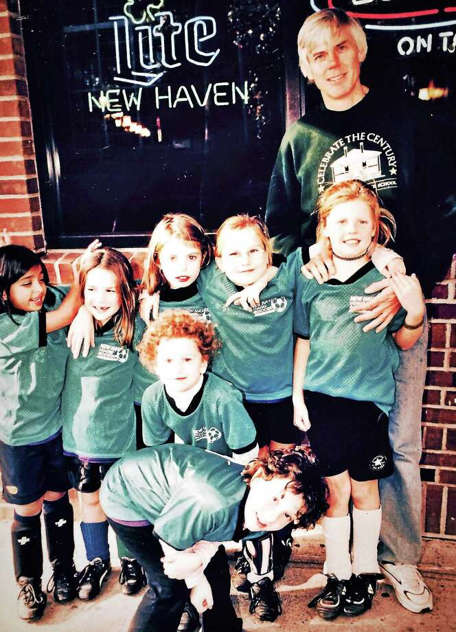 Randall Beach stands above his daughter, Charlotte, and her New Haven Youth Soccer teammates about 15 years ago outside Modern Pizza. Columnist Beach, a soccer novice, was the team's coach. Photo: Journal Register Co.