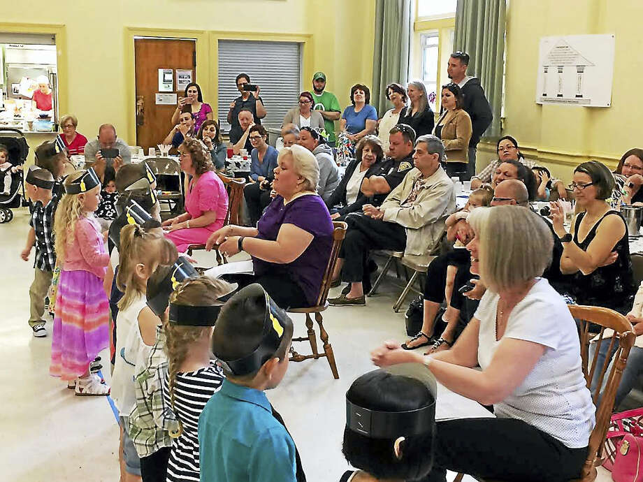 """West Haven Green Nursery School Director Jean Palmer, far left, and teachers Lynda Bennett and AnnMarie Sullivan -- who have taught at the school for 35 years, 21 years and 13 years, respectively -- lead the school's last 16 graduates in a round of songs on Friday. The kids all are wearing printed black-and-yellow paper """"mortarboards"""" on their heads. (Mark Zaretsky -- New Haven Register) Photo: Digital First Media"""