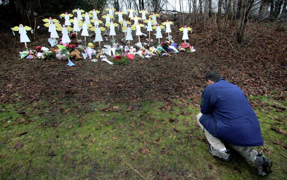 """FILE - In this Dec. 18, 2012, file photo, Robert Soltis, of Newtown, Conn., pauses after making the sign of the cross at a memorial to Sandy Hook Elementary School shooting victims in Newtown. The massacre in Newtown, in which a mentally troubled young man killed 26 children and teachers, served as a rallying cry for gun-control advocates across the nation. But in the three years since, many states have moved in the opposite direction, embracing the National Rifle Association's axiom that more """"good guys with guns"""" are needed to deter mass shootings. (AP Photo/Charles Krupa, File) Photo: AP / AP"""