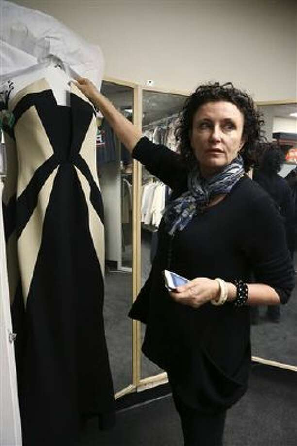 "In this Nov. 11, 2013 image released by ABC, Lyn Paolo, costume designer holds a Rubin Singer gown worn by Kerry Washington in the ABC drama series, ""Scandal,"" in the show's wardrobe closet on the Sunset Gower lot in the Hollywood section of Los Angeles. Photo: AP / American Broadcasting Companies,"