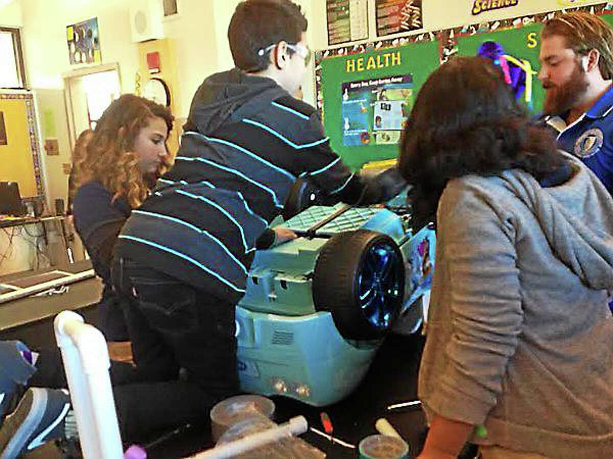 Celentano student Matthew Reyes-Lopez inspects the bottom of a robot-controlled toy car. (Brian Zahn - New Haven Register)