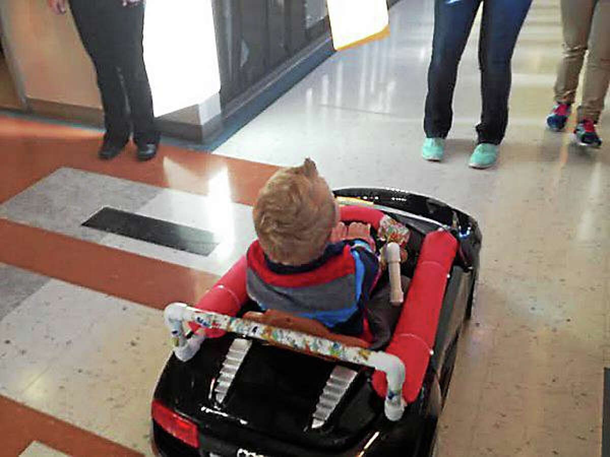 Nicholas Kelly, 3, rides through the hallways of Celentano in his new robot-controlled ride-on car. (Brian Zahn - New Haven Register)