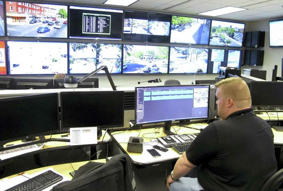 In this Friday, May 20, 2016 photo, Tyler Cullen, of Vulcan Security Technologies, looks at video screens in the Hartford police Real-Time Crime and Data Intelligence Center in Hartford, Conn. Staff at the center analyze data from surveillance cameras, gunshot detectors, license plate scanners and other sources. Vulcan Security Technologies helped set up the center. Such facilities are proliferating nationwide with the expanded use of surveillance technology, raising some concerns from civil liberties advocates. (AP Photo/Dave Collins) Photo: AP / Copyright 2016 The Associated Press. All rights reserved. This material may not be published, broadcast, rewritten or redistribu