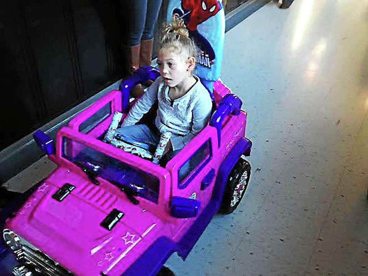 Cameron Werdann, 4, rides through the hallways of Celentano in her new robot-controlled car. (Brian Zahn - New Haven Register)