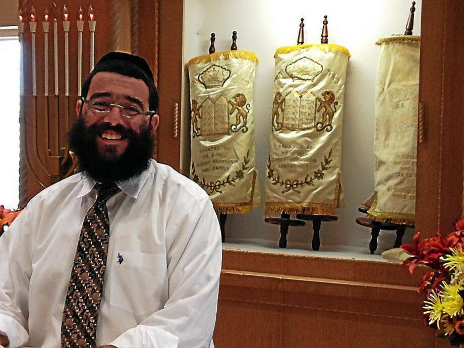 Rabbi Schneur Wilhelm stands by the Torah scrolls that miraculously survived a 2012 fire at Hebrew Congregation of Woodmont, which is being expanded and rebuilt. The scrolls are currently housed in a renovated activity center on the property, where services are bing held until the project is complete. Photo/Pam McLoughlin Photo: Journal Register Co.