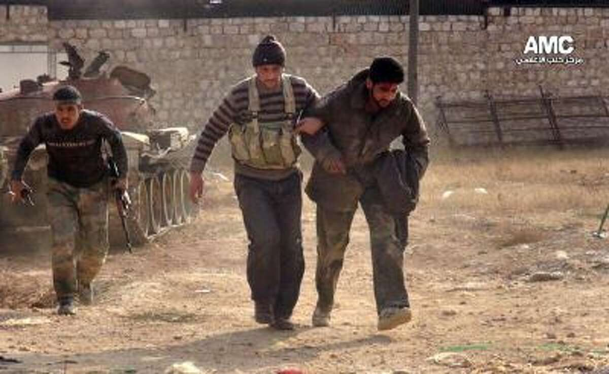 In this Monday, Nov. 11, 2013 file photo, citizen journalism image provided by Aleppo Media Center AMC, which has been authenticated based on its contents and other AP reporting, two Free Syrian Army fighters help a wounded comrade during clashes in Aleppo, Syria.