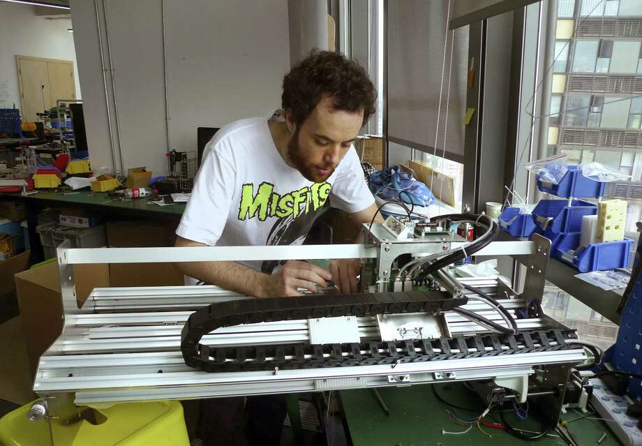 "(Kelvin Chan — The Associated Press) Gerard Rubio, CEO of London-based startup Kniterate, works on a prototype for an automated knitting machine his company is developing at the Hax hardware startup ""accelerator"" in Shenzhen, China. Photo: AP / Copyright 2016 The Associated Press. All rights reserved. This material may not be published, broadcast, rewritten or redistribu"