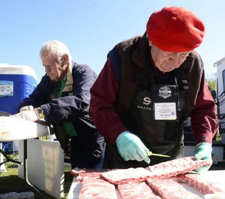 "Pitmasters Mike Mills, left, and Pat Burke with the Apple City Barbecue Team trim some of their meat Friday in preparation for Saturday's competition. The Apple City Team was part of the ""Winners Circle"" competition which brought back the grand champions from the previous 24 competitions. The Apple City team won The Jack in 1992."