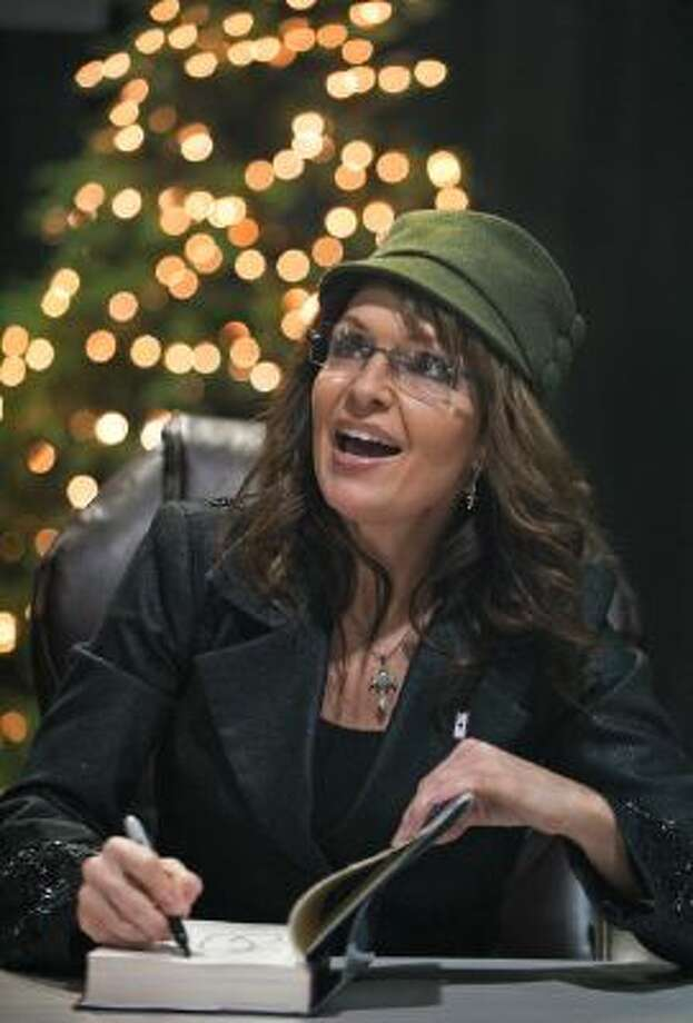 """Former Alaska Governor and Republican vice presidential candidate Sarah Palin autographs copies of her recently released book """" Going Rogue: An American Life"""", sitting in front of a Christmas Tree on December 5, 2009, inside the BJ's discount warehouse in the Fair Lakes shopping mall in Fairfax, Virginia. Photo: AFP/Getty Images / 2009 AFP"""