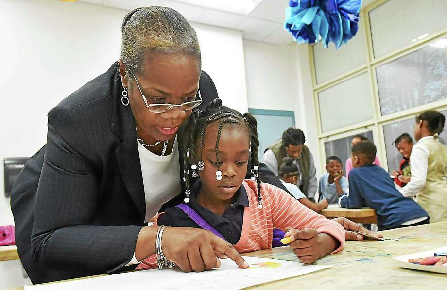(Catherine Avalone - New Haven Register)  Principal Janet Brown-Clayton stopped in at the art class during the after school program at the Lincoln-Bassett School in New Haven and offered to help Ariana Parks, 8, a third grade student with her art project Monday afternoon, November 10, 2014. Photo: Journal Register Co. / New Haven RegisterThe Middletown Press