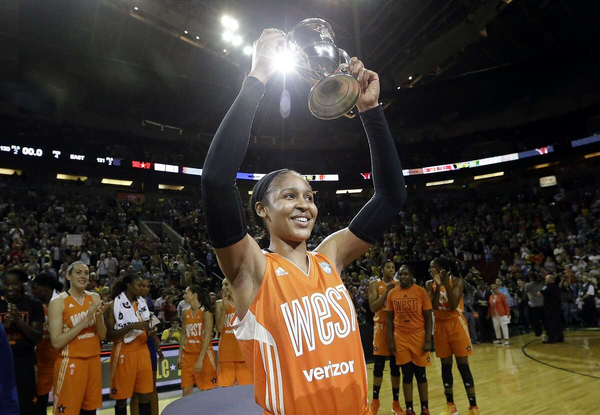 Minnesota Lynx's Maya Moore, of the Western Conference, holds up a trophy after being named most valuable player as teammates cheer behind after the WNBA All-Star basketball game Saturday, July 22, 2017, in Seattle.(AP Photo/Elaine Thompson)