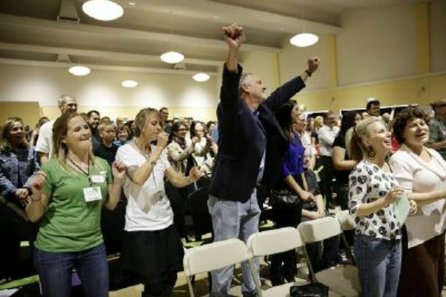 Attendees sing a song at the Sunday Assembly, a godless congregation founded by British comedians Sanderson Jones and Pippa Evans, on Sunday, Nov. 10, 2013, in Los Angeles.