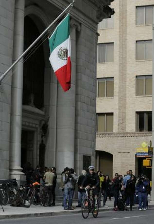 Cyclist Carlos Gutierrez, a double amputee, rides his bike past the Mexican Consulate, Thursday, Nov. 7, 2013, in San Antonio.