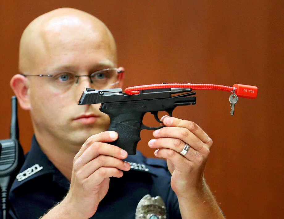 FILE- In this June 28, 2013, file photo, Sanford police officer Timothy Smith holds up the gun that was used to kill Trayvon Martin, while testifying in the George Zimmerman trial, in Seminole circuit court in Sanford, Fla. The pistol former neighborhood watch volunteer Zimmerman used in the fatal shooting of Martin is going up for auction online. (AP Photo/Orlando Sentinel, Joe Burbank, Pool, File) Photo: AP / Pool Orlando Sentinel