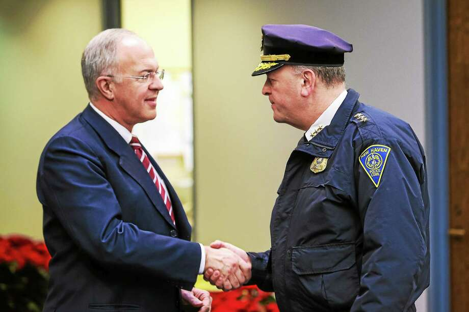 (Contributed photo) New Haven-based Knights of Columbus Supreme Knight Carl Anderson, left, shakes hands with New Haven Police Chief Dean Esserman, at Coats for Kids event Photo: Journal Register Co. / © www.mikerossphoto.com