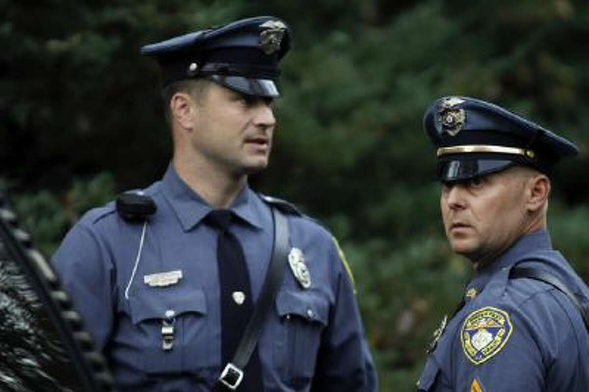 Two local law enforcement officers talk in the driveway of a home belonging to the father of the LAX shooting suspect, Paul Ciancia, in Pennsville N.J. on Friday Nov. 1, 2013.