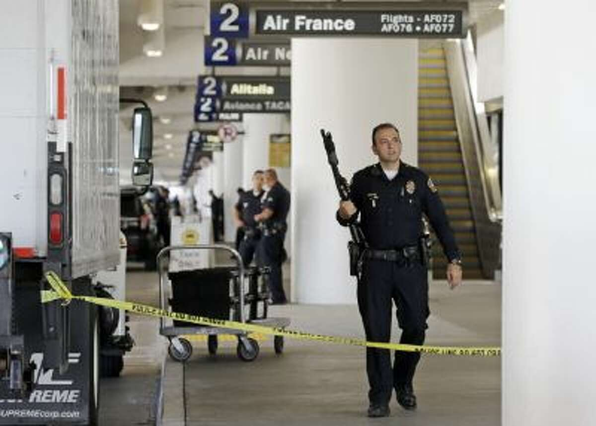 Police stand guard in Terminal 2 at Los Angeles International Airport on Friday, Nov. 1, 2013.