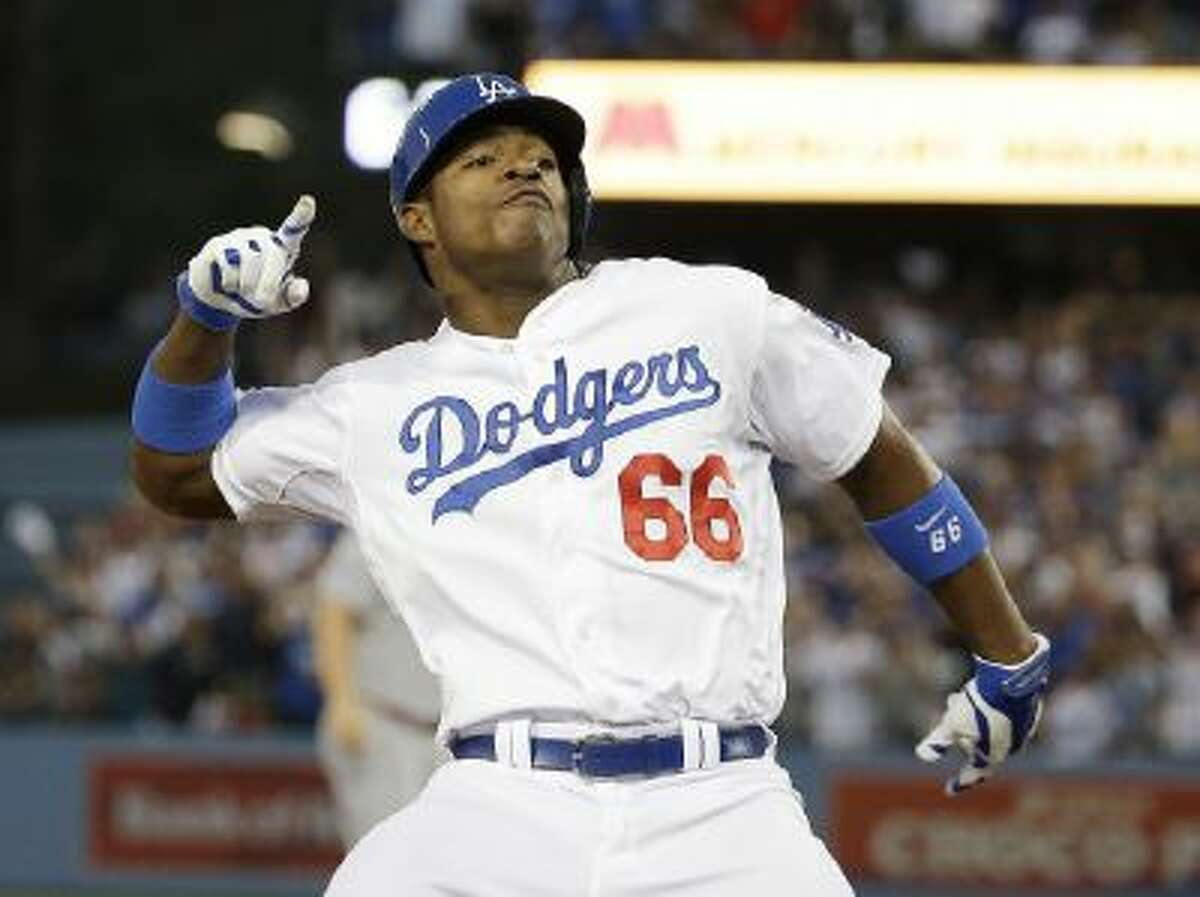 Los Angeles Dodgers' Yasiel Puig reacts after hitting a run-scoring triple during the fourth inning of Game 3.