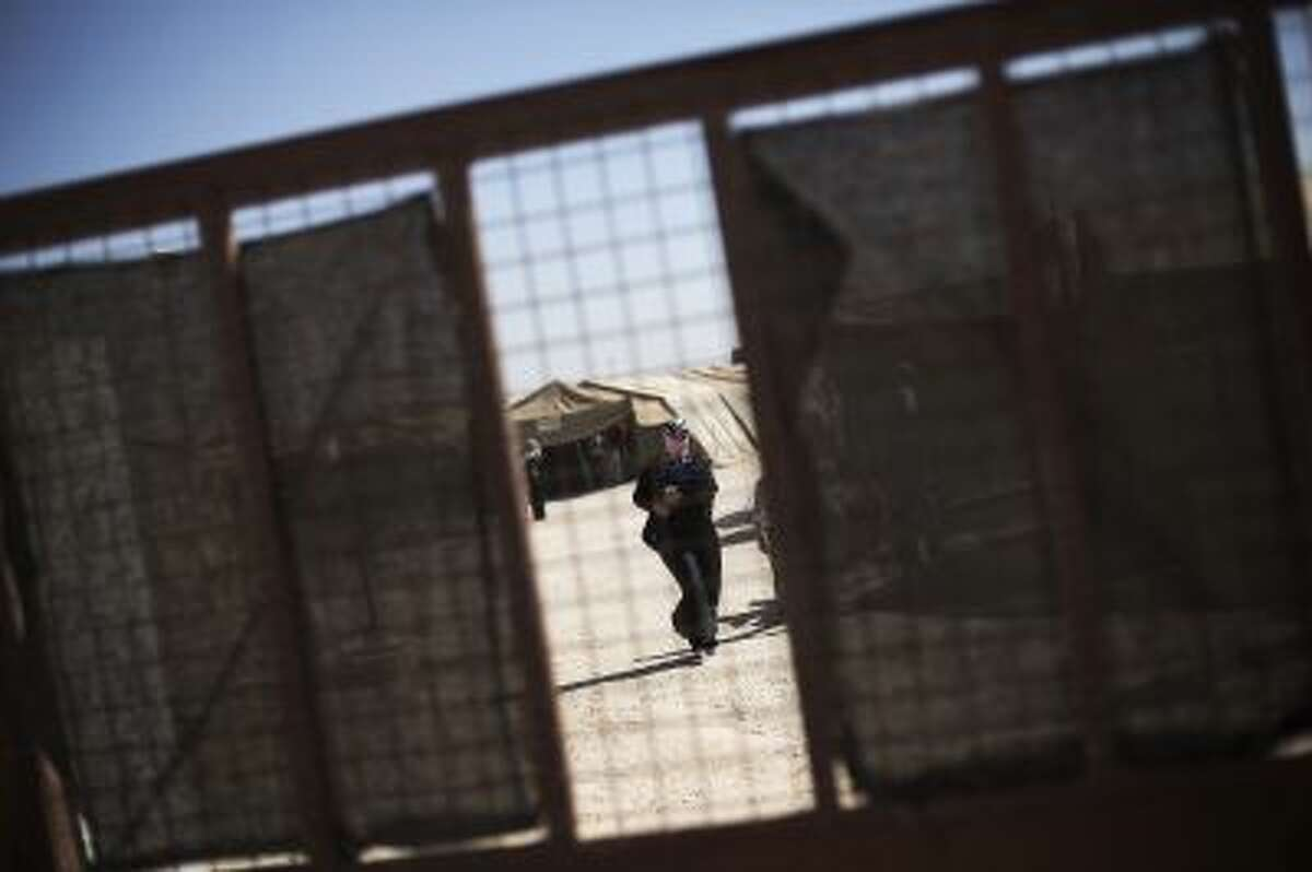 In this Thursday, Oct. 24, 2013, photo, a Syrian woman walks inside the Morocco Royal Army campaign hospital at the Zaatari refugee camp, near the Syrian border in Jordan. The camp has three schools, two hospitals and a maternity clinic. (AP Photo/Manu Brabo)