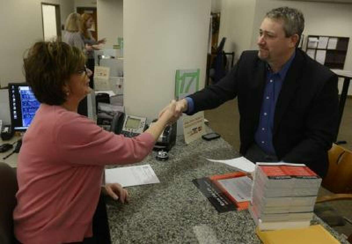 Shawn Phillips, right, owner of Strainwise marijuana stores, shakes hands with Denver Excise and License technician, Jennifer Scott, left, Friday morning, Dec. 27, 2013 after receiving his license to legally sell marijuana.