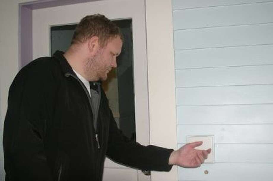 Implantable technology proponent Amal Graafstra of Seattle demonstrates how one of the doors to his home can be unlocked by passing either of his hands past a sensor which reads the signal from an implanted RFID chip. Photo: (Courtesy Of Amal Graafstra)
